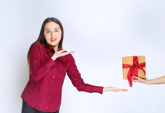 Изображение модели молодой женщины, указывая на подарок с бантом на белой стене.