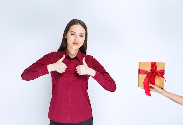 弓を持ったプレゼントの近くで親指を立てている若い女性モデルの画像。