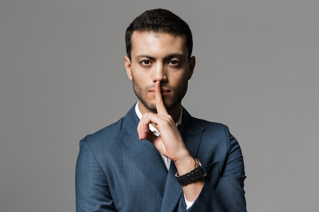 회색 벽 위에 절연 입술에 검지 손가락을 들고 공식적인 소송에서 성인 아랍어 사업가 30 대의 이미지