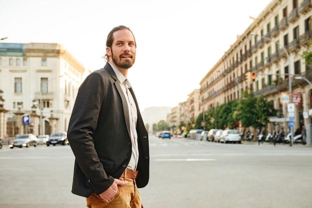 Изображение взрослого привлекательного мужчины с волосами на лице в куртке, смотрящего в сторону, пересекая проспект в центре города