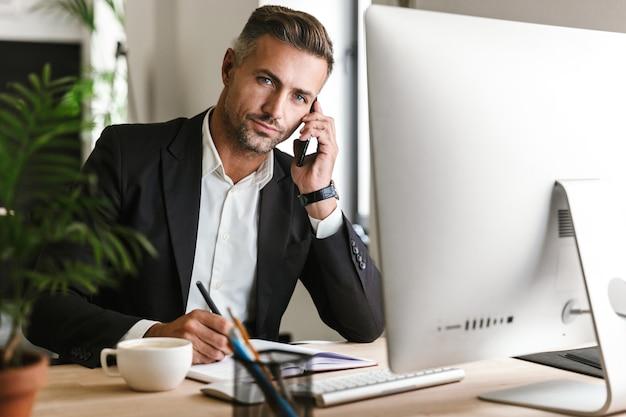 사무실에서 컴퓨터에서 작업하는 동안 휴대 전화로 이야기하는 양복을 입고 성인 사업가 30 대의 이미지