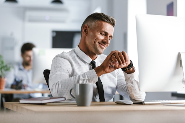 Изображение взрослого бизнесмена 30-х годов в белой рубашке и галстуке, сидящего за столом в офисе за компьютером и смотрящего на наручные часы