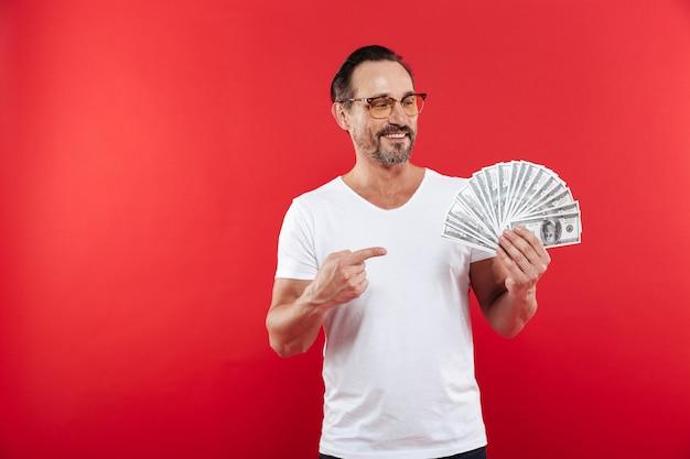赤い背景に分離された眼鏡を笑顔でたくさん手に持ってお金賞金ドル通貨で指を指しているカジュアルな白いtシャツで成人男性30代のイメージ