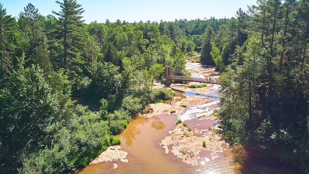 현수교와 2명의 등산객이 있는 녹색 숲의 큰 갈색 강을 따라 공중으로 내려가는 이미지