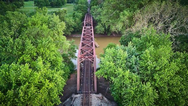 푸른 나무가 있는 갈색 강 위의 기차 트랙을 위한 보라색 금속 다리의 공중 이미지