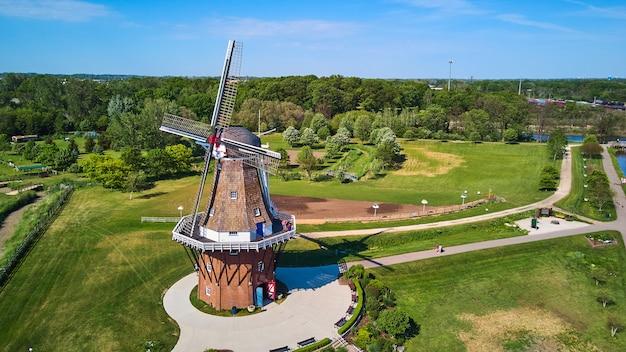 Изображение ветряной мельницы на чистой зеленой лужайке с воздуха