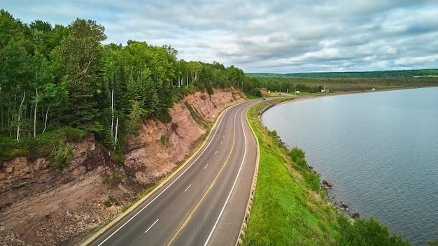 湖の周りを回る道路と緑の森のある岩の崖の端に向かって空撮の画像