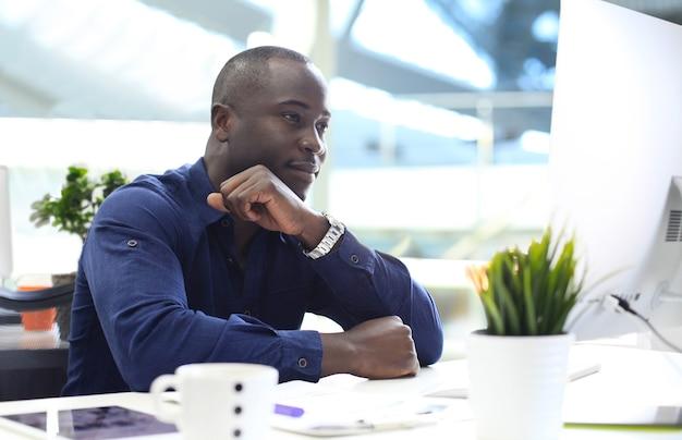 Изображение афро-американского бизнесмена, работающего на компьютере.