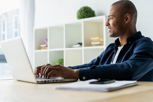 그의 노트북에서 작업 하는 아프리카계 미국인 사업가의 이미지. 그의 책상에 잘생긴 젊은 남자.