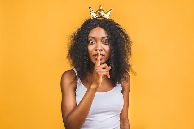 人差し指を唇に持ち、黄色の背景の上に沈黙を隔離するように求めているカジュアルな服装のアフリカの女性20代の画像。