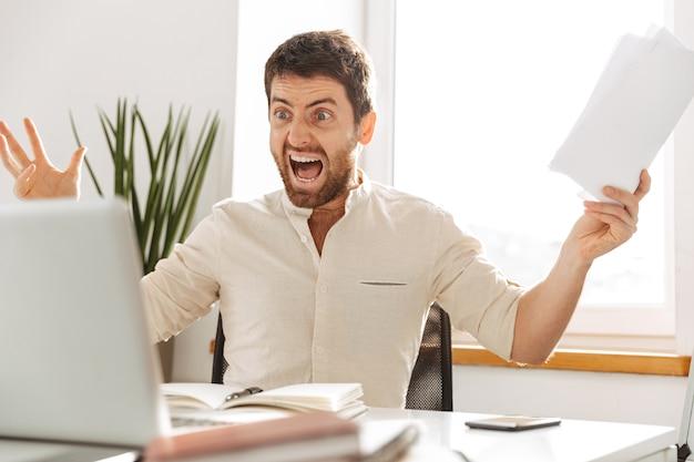Изображение агрессивного офисного работника 30-х годов в белой рубашке, использующего ноутбук и бумажные документы на современном рабочем месте