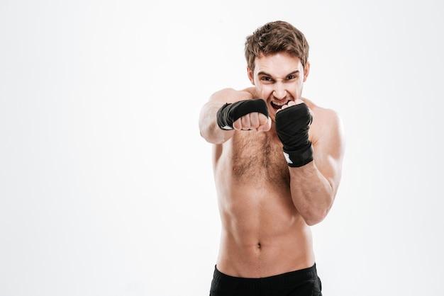 Изображение агрессивного боксера молодого человека делает упражнения бокса над белой стеной.