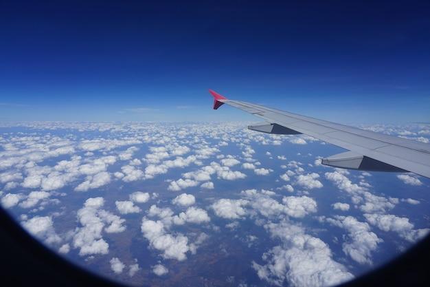 飛行機の窓からの飛行機の翼と雲の画像
