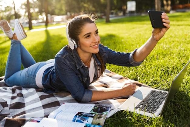 Изображение удивительной красивой молодой женщины-студента в парке с помощью портативного компьютера, слушающего музыку в наушниках, делает селфи по телефону.