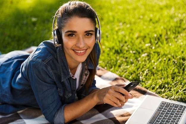 Изображение студента удивительной красивой молодой женщины в парке с помощью портативного компьютера, прослушивания музыки с наушниками, с помощью мобильного телефона.