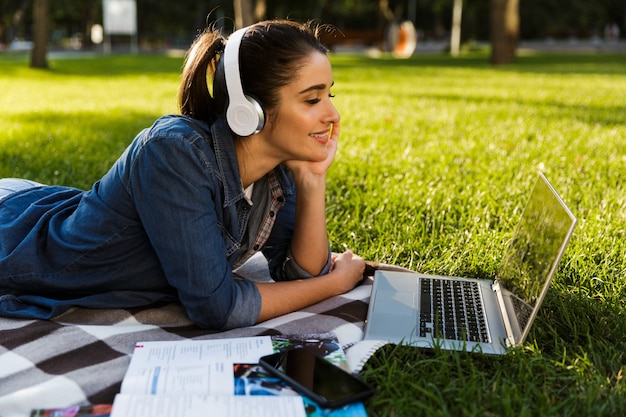 Изображение студента удивительной красивой молодой женщины в парке, используя музыку портативного компьютера слушая с наушниками.