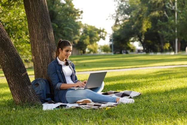 Изображение удивительно красивой молодой женщины студента в парке с помощью портативного компьютера.