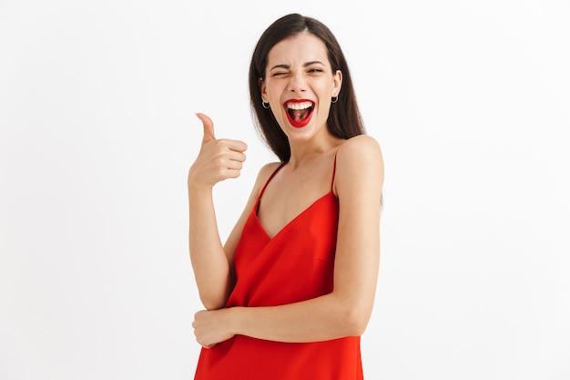 親指を立てるジェスチャーを示す孤立したポーズをとる驚くべき感情的な若い美しい女性の画像。