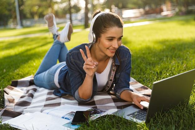 Изображение удивительной счастливой студентки женщины лежит на открытом воздухе в парке, используя музыку портативного компьютера, слушая, делая жест мира.