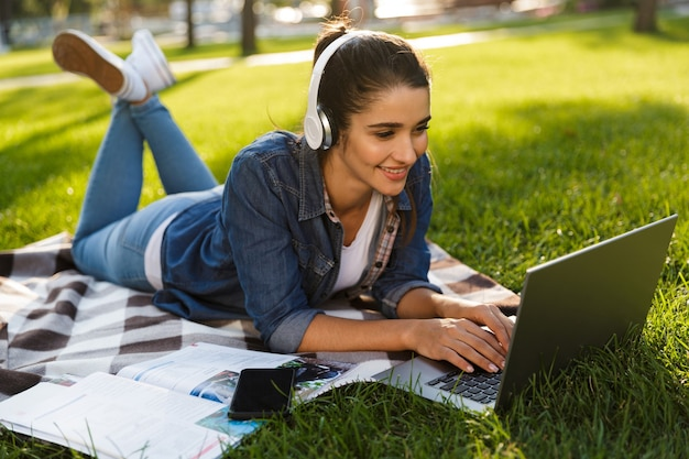 Изображение удивительно счастливой студентки женщины лежит на открытом воздухе в парке, используя музыку портативного компьютера слушая.