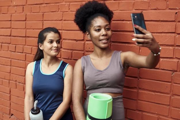 벽돌 벽에 셀카를 복용 놀라운 젊은 운동 여성의 이미지. 웃는 흑인 여성은 스포츠 운동 후 함께 시간을 보냅니다.