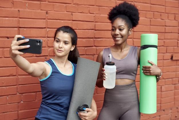벽돌 벽에 셀카를 찍는 놀라운 젊은 운동 여성의 이미지. 웃고 있는 흑인 여성들은 운동 후 함께 시간을 보낸다.