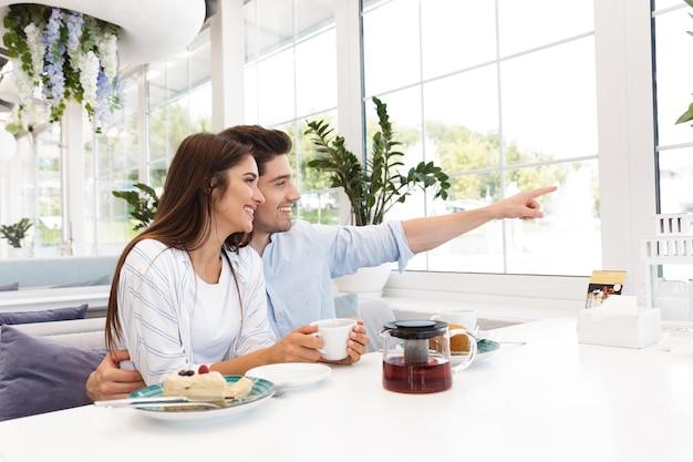 カフェに座っている驚くべき若い愛情のあるカップルの画像は、デザートを食べて、指さしを脇に見てお茶を飲みます。
