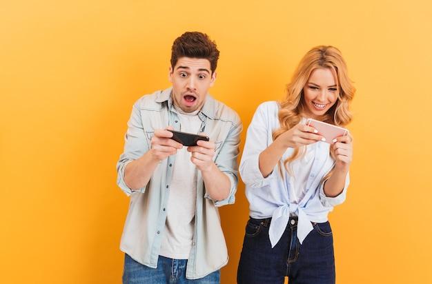 面白い若いカップルの男性と女性が携帯電話でビデオゲームを一緒に遊んでの画像