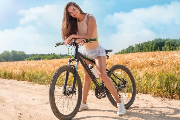 Изображение привлекательной счастливой женщины на велосипеде. концепция спортивного образа жизни. смешанная техника