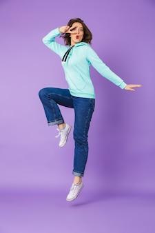 Изображение возбужденной красивой молодой женщины, позирующей изолированной над фиолетовой стеной, прыгающей на стене, показывающей мир.