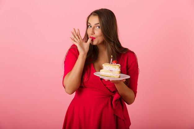 케이크를 들고 핑크 벽 위에 절연 흥분된 배고픈 젊은 여자의 이미지.