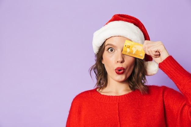 Изображение возбужденной потрясенной молодой женщины в рождественской шляпе, изолированной над фиолетовой стеной, держащей дебетовую карту.