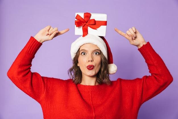 Изображение возбужденной шокированной молодой женщины в рождественской шляпе, изолированной над фиолетовой стеной, держащей подарочную коробку-сюрприз.
