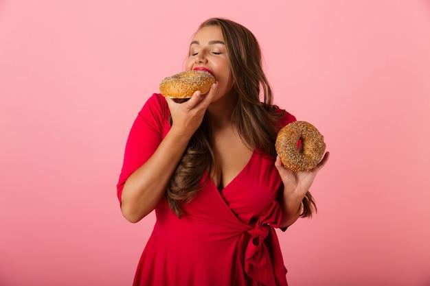 Изображение возбужденной молодой женщины, изолированной над розовой стеной, ест пончики.