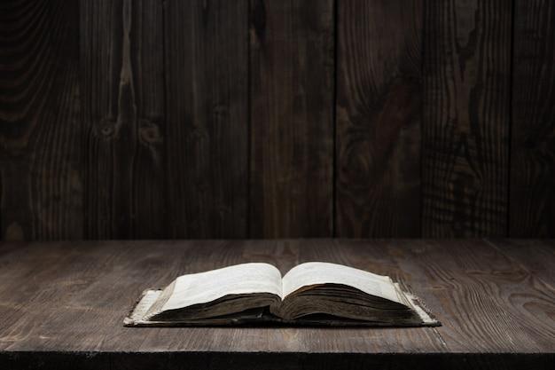 어두운 공간에서 나무 배경에 나무 배경에 오래 된 성경의 이미지
