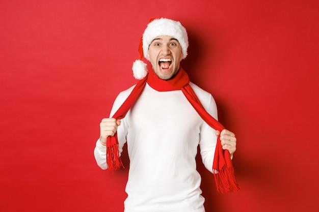 怒っている大人の男性の画像は、スカーフとサンタの帽子をかぶってクリスマスを嫌い、苦しんで立っている狂牛病を叫んで...