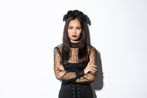 怒って気分を害したアジアの女の子が何かに不平を言ったり、腕を組んだり、やめたりする画像