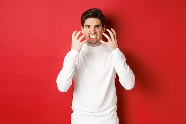 怒り狂って立っている怒りから顔をゆがめ、揺れている白いセーターを着た怒り狂った男の画像...