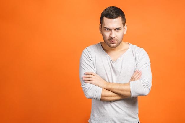 オレンジ色の背景の壁の上に孤立して立っている怒っている不機嫌な男の画像