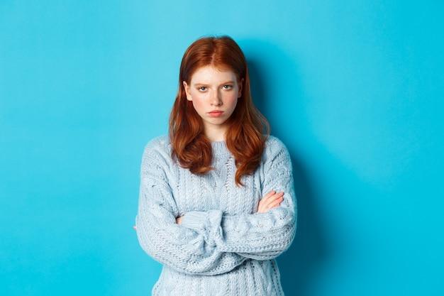 怒っている赤毛の女の子が気分を害し、胸に腕を組んでしゃがみ、カメラを狂わせて見つめ、青い背景に立っている画像。