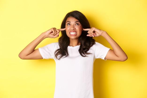 짜증나고 짜증나는 아프리카계 미국인 소녀의 이미지는 귀를 닫고 불평하는 화난 표정