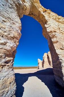 푸른 하늘이 있는 사막에서 흰 돌을 통해 아치의 이미지