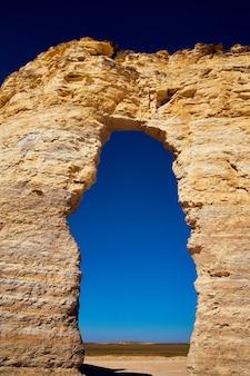 대담한 푸른 하늘 그라데이션으로 자연석 벽을 절단하는 아치 밑의 통로 이미지