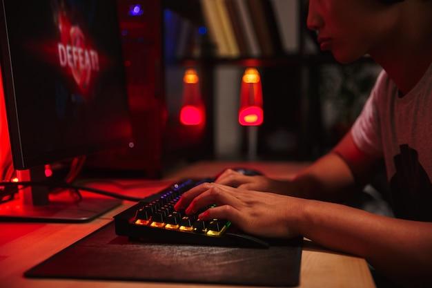 暗い部屋でコンピューターで遊んでいる間、ヘッドフォンを着用し、バックライト付きのカラフルなキーボードを使用してビデオゲームを失うアジアの10代のゲーマー少年の画像