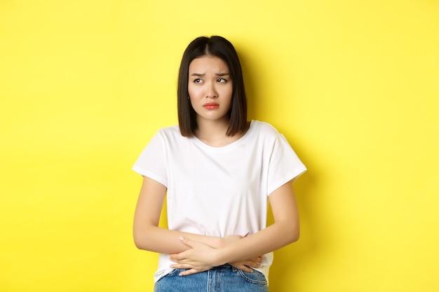 Изображение азиатской женщины, которая плохо себя чувствует, испытывает болезненные спазмы, держится за руки на животе и хмурится от боли, дискомфорта во время менструального цикла, стоит на желтом фоне.