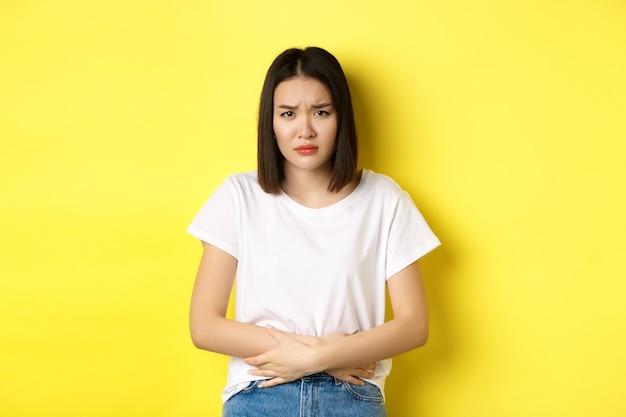 Изображение азиатской женщины, которая плохо себя чувствует, испытывает болезненные спазмы, держится за руки на животе и хмурится от боли, дискомфорта во время менструального периода, стоит на желтом фоне.
