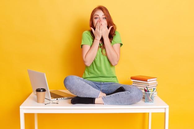 練習帳、ラップトップ、ペン、コーヒーで勉強しながら叫んでびっくりした10代の少女の画像。組んだ足でテーブルに座って驚いた学生。