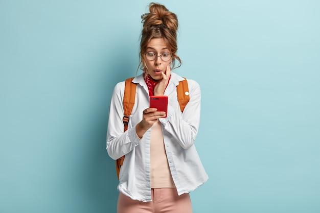 Изображение изумленной молодой женщины, пристрастившейся к интернету, сети через мобильный телефон, удивленной ограничениям, с темными зачесанными волосами