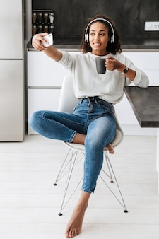 明るいキッチンに座って、自分撮り写真を撮るヘッドフォンを身に着けている魅力的なアフリカ系アメリカ人の女の子の画像