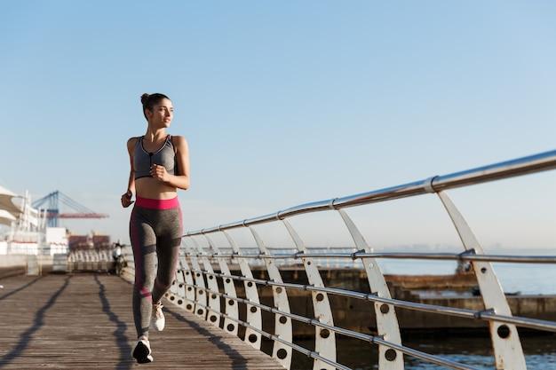 朝ジョギング、海を見て、笑顔のスポーツウェアで魅力的なアスリート女性の画像